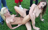 Naked girls finger and lick each other outdoors while 3 guys watch